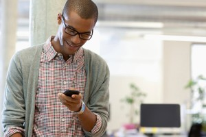 Man in office looking at phone